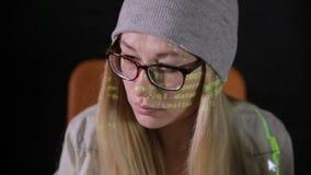 Jovem mulher séria que usa o computador na noite na sala escura Código de computador refletido em sua cara filme