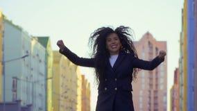 A jovem mulher salta da felicidade na rua, slowmotion filme
