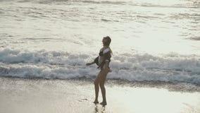 A jovem mulher salta e exulta na praia do mar filme