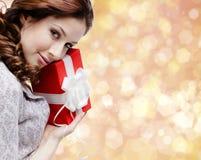 A jovem mulher é satisfeita com um presente do Natal Imagens de Stock Royalty Free