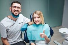 A jovem mulher satisfeita feliz senta-se no carvão animal e no sorriso Mantém o polegar grande Suporte masculino do dentista ao l imagem de stock royalty free