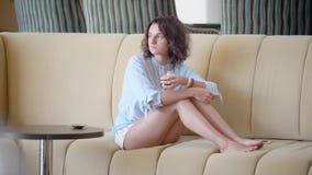 Jovem mulher satisfeita que refrigera no sofá e no chá de refrescamento bebendo vídeos de arquivo