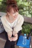 Jovem mulher satisfeito que senta-se olhando algo Fotos de Stock