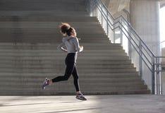 Jovem mulher saudável que corre no ambiente urbano Fotos de Stock