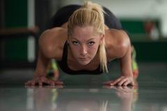 Jovem mulher saudável que faz Impulso-UPS no assoalho Imagens de Stock Royalty Free