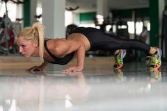 Jovem mulher saudável que faz Impulso-UPS no assoalho Foto de Stock