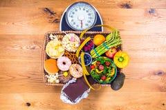 Jovem mulher saudável que olha alimento saudável e insalubre, tentando fazer a escolha direita foto de stock