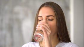 Jovem mulher saudável que toma a medicina em casa Tomando comprimidos com água 4 K filme