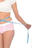 Jovem mulher saudável que verifica sua perda de peso com uma fita métrica Fotos de Stock
