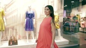 Jovem mulher segura atrativa que gira circularmente ao andar ao longo das lojas da roupa filme