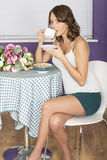 Jovem mulher segura feliz atrativa que come o café bebendo do café da manhã Imagem de Stock