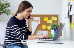 Jovem mulher segura que trabalha em seu escritório com portátil imagem de stock