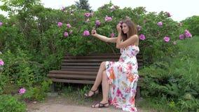 Jovem mulher Selfie com as flores que sentam-se no banco filme