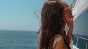 Jovem mulher sensual no biquini no iate privado caro no oceano no movimento lento filme
