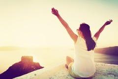 A jovem mulher senta-se com mãos que admira acima Santorini, Grécia Imagens de Stock Royalty Free