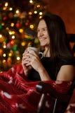 A jovem mulher senta-se em uma balançar-cadeira perto da Natal-árvore fotografia de stock