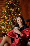 A jovem mulher senta-se em uma balançar-cadeira perto da Natal-árvore fotos de stock