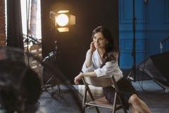 A jovem mulher senta-se em uma cadeira no estúdio da foto fotos de stock royalty free