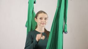 A jovem mulher senta-se em uma mulher de sorriso da rede que mostra o que me chame sinal Exercício aero aéreo do instrutor da apt video estoque