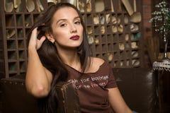A jovem mulher senta-se em uma poltrona Foto de Stock Royalty Free