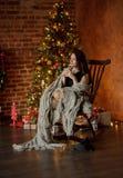 A jovem mulher senta-se na balançar-cadeira perto da Natal-árvore fotografia de stock