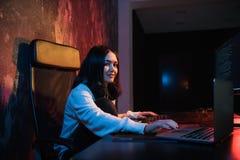 A jovem mulher senta-se na frente do computador pessoal e do portátil, PHP que programa o conceito do Cyberspace da codificação d fotografia de stock royalty free