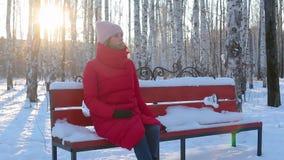 A jovem mulher senta-se no banco e na neve dos toques no parque pictórico da cidade com vidoeiros filme