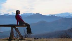 A jovem mulher senta-se no banco fora e no olhar na paisagem pictórico com montanhas video estoque