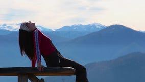 A jovem mulher senta-se no banco fora e no olhar na paisagem pictórico com montanhas vídeos de arquivo