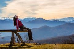 A jovem mulher senta-se no banco fora e no olhar na paisagem pictórico com montanhas fotos de stock royalty free