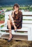 A jovem mulher senta-se no banco na paisagem natural, desejo por viajar imagens de stock