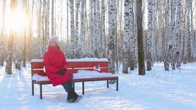 A jovem mulher senta-se no banco no parque pictórico da cidade com os vidoeiros no inverno vídeos de arquivo