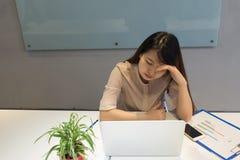 A jovem mulher sente forçada no trabalho fotografia de stock royalty free