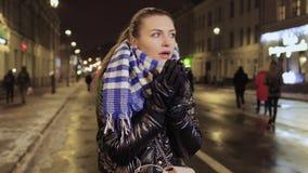 A jovem mulher sente fria e espirrando durante a espera seus amigos na rua urbana vídeos de arquivo