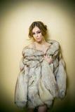 Jovem mulher 'sexy' atrativa que veste um casaco de pele que levanta provocatively interno Retrato da fêmea sensual com corte de  Fotos de Stock