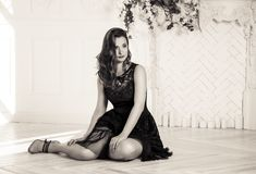 A jovem mulher 'sexy' bonita no vestido preto está sentando-se no assoalho Mulher elegante nova no vestido preto Foto de Stock Royalty Free