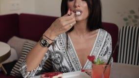 Jovem mulher 'sexy' bonita que aprecia comendo o bolo apetitoso da pastelaria usando a inclinação da forquilha acima vídeos de arquivo