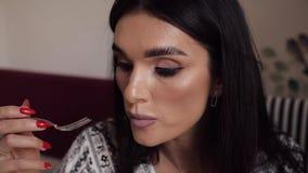 Jovem mulher 'sexy' bonita que aprecia comendo o bolo apetitoso da pastelaria usando a inclinação da forquilha acima filme