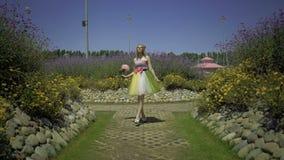 A jovem mulher 'sexy' feliz com a flor mindinho grande está andando no passeio no jardim Consideravelmente sonhando a menina boni video estoque