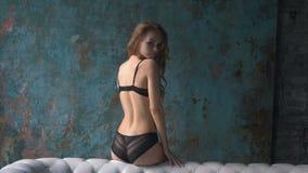 Jovem mulher 'sexy' na roupa interior na sala de visitas com parede do grunge vídeos de arquivo