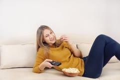 Jovem mulher smilling bonito que olha a tevê e que relaxa no sofá em ho Fotografia de Stock Royalty Free