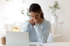 Jovem mulher sombrio que senta-se na mesa que olha o tela de computador imagens de stock royalty free
