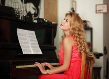 Jovem mulher sonhadora que senta-se no piano na sala imagens de stock