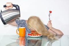A jovem mulher sonolento comeu o café da manhã e pôs sua cabeça em uma placa, caiu adormecido em uma placa Derrama a água em uma  imagem de stock royalty free
