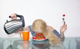 A jovem mulher sonolento comeu o café da manhã e pôs sua cabeça em uma placa, caiu adormecido em uma placa Derrama a água em uma  fotografia de stock royalty free