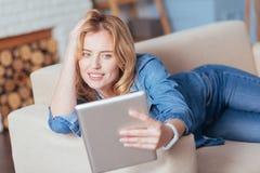 Jovem mulher surpreendente que toma uma foto ao descansar em um sofá imagem de stock