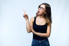 Jovem mulher surpreendida bonita com exibição dos monóculos e apontar sobre o fundo branco foto de stock