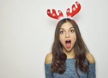 Jovem mulher surpreendida com os chifres da rena em sua cabeça com a boca aberta no fundo branco fotos de stock