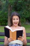 A jovem mulher surpreendida com yeas extensamente abertos e boca está lendo um livro fora fotografia de stock
