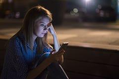 Jovem mulher surpreendida e preocupada que obtém más notícias no smartphone Fotografia de Stock